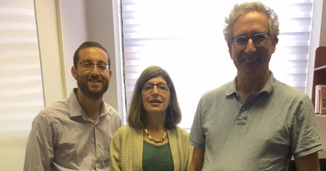 Three cheerful academics look directly at the camera