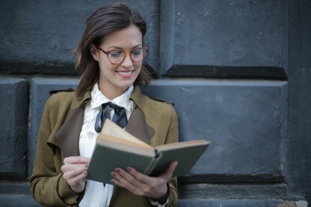 Cheerful female scholar reads an academic manuscript outdoors