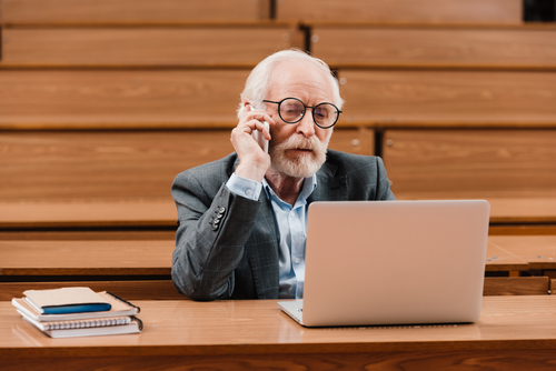 Mature student engages in online research in lecture hall