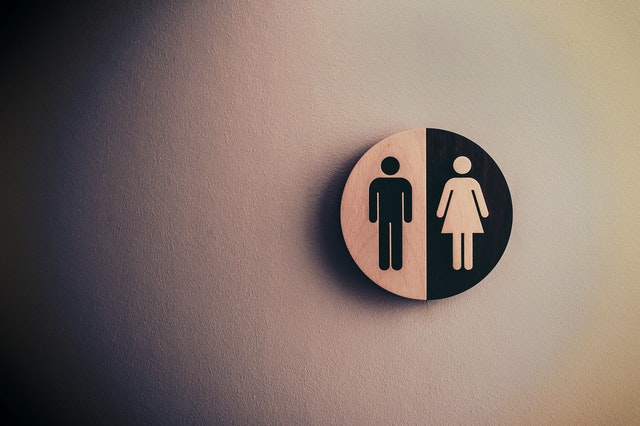 A gender neutral sign accompanied by the word 'everyone' is glued onto toilet door