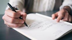 Man writes in notepad
