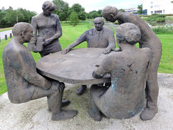Statues of men and women appear to be discussing research ideas in local park