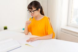 Female academic translator uses academic dictionary to complete a translation