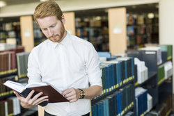 Man looks at research book