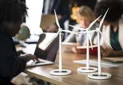 Academic researchers are surrounded by several miniature models of wind turbines