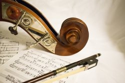 The handle of a cello along with the cello bow lies on a piece of music