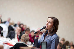 Female academic speaking from a podium delivers a conference