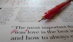A fine line pen rests on the edited version of an author's article