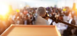 A close-up of a microphone as an academic conference is about to take place