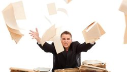 Frustrated man throws research papers up in the air