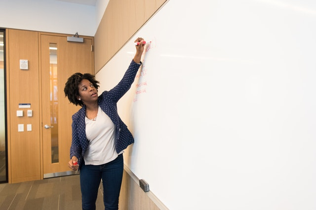 Academic writes on whiteboard in lecture hall