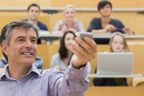 Lecturer holds up presentation clicker in the presence of his students