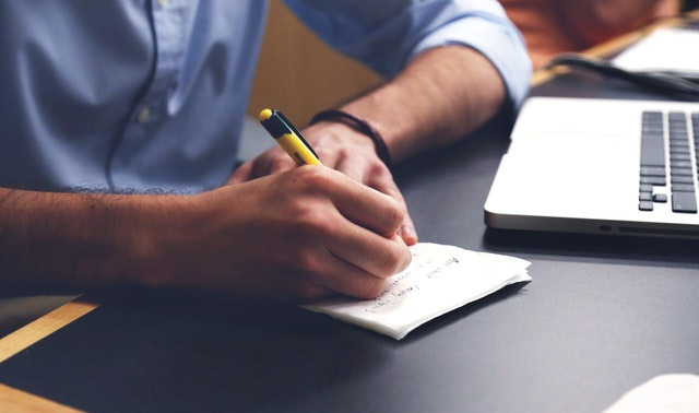 Academic translator writes down notes before conducting research